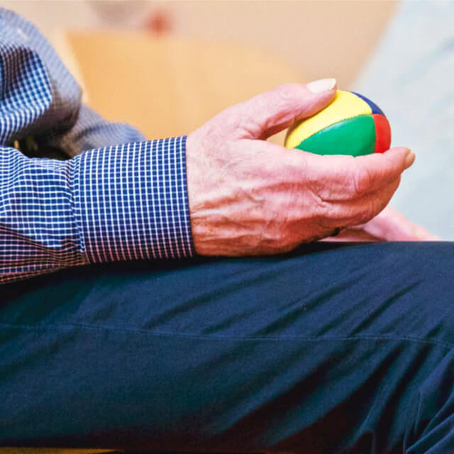 Man Holding a ball at a physical therapy session.